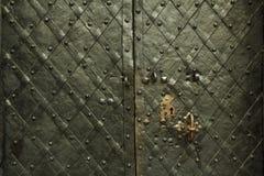 Textura forjada antiga do metal com folhas de prova decorativas Portas, portas, obturadores Detalhe de uma porta cinzenta medieva imagens de stock royalty free