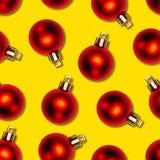 Textura inconsútil de las bolas rojas de la Navidad en fondo amarillo Fotos de archivo libres de regalías