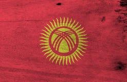 Textura kirguizia de la bandera del Grunge, campo rojo con un sol amarillo con cuarenta rayos uniformemente espaciados stock de ilustración