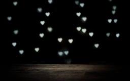 textura marrón de madera en fondo oscuro con los corazones que brillan intensamente Fotografía de archivo