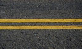 Textura oscura del asfalto con las líneas amarillas Fotografía de archivo libre de regalías