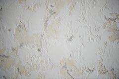 A textura, a parede cremosa, é marcado pelas manchas brancas da massa de vidraceiro fim fotografia de stock