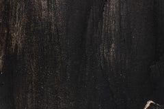 Textura pintada preta do metal com borrões, riscos e sparkles do ouro fotografia de stock