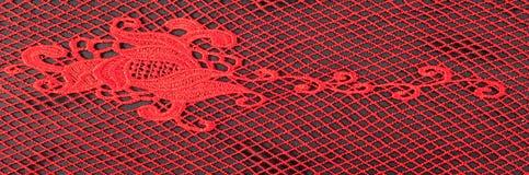 Textura, teste padrão vermelho do laço da tela, em um fundo preto Um bea Imagem de Stock Royalty Free