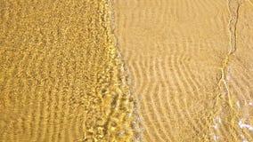 textura transparente del fondo del alivio del canto de la agua de mar de las ondas bajas costeras de la arena Foto de archivo libre de regalías