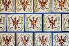 Textura um azulejo branco quadrado bonito com testes padrões sob a forma de um pássaro, águia, galo com emendas azuis O fundo fotografia de stock