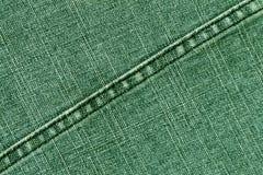 Textura verde del paño de los vaqueros con la puntada Fotografía de archivo