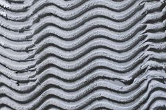 Textural monophonic background of plaster plaster gray, with a pattern in the form of waves royalty free stock images