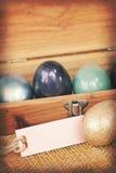 Texturas del papel del vintage, huevo de Pascua colorido en la caja de madera con la etiqueta de papel Imagenes de archivo