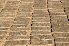 texturbakgrund av den kullersten stenlade gatan Arkivbild