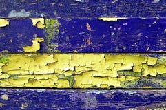 Texturbakgrund - gammal målad träyttersida med skalningslilor och guling målar Royaltyfri Bild