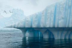 Texture à colonnes bleue unique d'art d'iceberg de l'Antarctique avec le point pointu sous le ciel nuageux MONTAGNES DE MILOU photos stock