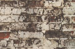 Texture of aged red brick wall painted white color with cracked weathered structure close-up. Texture of brick wall with cracked weathered structure red white royalty free stock photo
