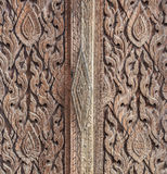 Texture of an ancient wooden door in a Thai temple. Closer shot to display the texture of an ancient wooden door. It is located in a public temple called Wat Royalty Free Stock Image
