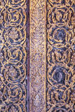 Texture on an antique door at Thai temple. The texture and design of the antique door at Wat Yai Suwannaram in Petchburi, Thailand. The damage on the upper right Stock Image