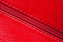 The texture of the artificial patent leather is red with an embedded zipper.  stock photography