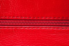 The texture of the artificial patent leather is red with an embedded zipper.  royalty free stock photo