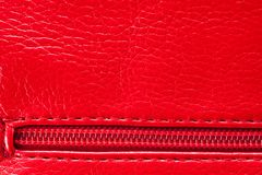 The texture of the artificial patent leather is red with an embedded zipper.  royalty free stock photography