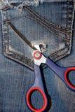 Texture as tesouras que cortam um furo em seu bolso Foto de Stock Royalty Free