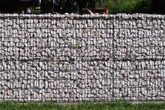 Texture for the background of a backdrop of a freely lying stone supported by a metal mesh. Technology of construction of fences f. Rom natural materials Royalty Free Stock Image