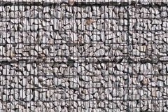 Texture for the background of a backdrop of a freely lying stone supported by a metal mesh. Technology of construction of fences f. Rom natural materials Royalty Free Stock Photography