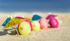 Texture (background) with colorful easter eggs with umbrellas on the beach with sea. Sand texture (background) with colorful easter eggs with umbrellas on the Stock Photo