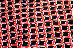 Texture, background, pattern. Fabric drawing of a diamond diamond red on a black background stock photo