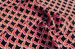Texture, background, pattern. Fabric drawing of a diamond diamond red on a black background royalty free stock photo