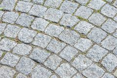 Texture, background. The pavement of granite stone. Paved roadway street. any paved area or surface. Old cobblestone road. Pavement texture, grass between stock photography