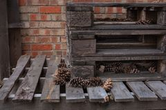 Stacked wood palettes with brick background. Texture background stacked wood palettes with brick background and pine cones Royalty Free Stock Photos
