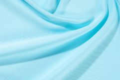 Texture. Background. Template. Pamper your design with a luxurious light blue silk flag. The blue dip can boast of a dull sheen. And a crisp hand. His stiff royalty free stock photo
