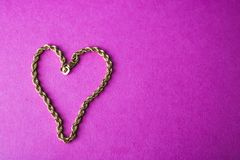 Texture of a beautiful golden festive chain unique weaving in the shape of a heart on a pink purple background and copy space. stock photos