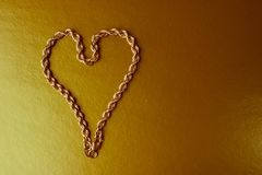 Texture of a beautiful golden festive chain unique weaving in the shape of a heart on a yellow gold background and copy space. Concept: love, marriage proposal stock photography
