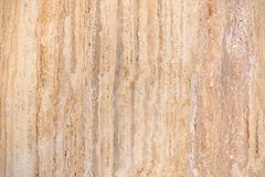 Beige brown stone slab with vertical pattern. Texture of a beige and brown stone slab with vertical pattern, taken in close-up Stock Image