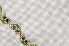 Texture of Beige Linen Fabric with Embroidery. Handmade Embroidery by Cross Stitch in the View of Acorns. Texture of Beige Natural Linen Fabric with Embroidery Royalty Free Stock Photo