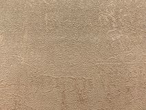 Texture of beige wallpaper with a pattern. Texture of light brown plush wallpaper with a pattern. Textile bronze surface, structure close-up Royalty Free Stock Image