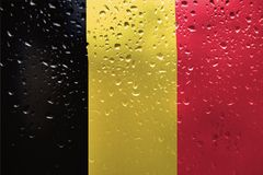 Texture of Belgium flag. Texture of Belgium flag on the glass with drops of rain at dawn stock photography