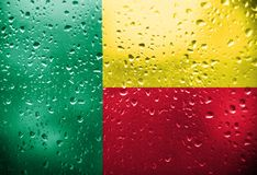 Flag of Benin. Texture of Benin flag on the glass with drops of rain stock images