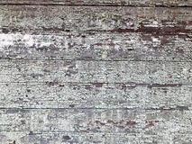 Texture of a black gray old dilapidated wooden wall, a fence with pieces of old shabby exfoliated paint from horizontal worn-out r. Otten boards with cracks and Stock Images