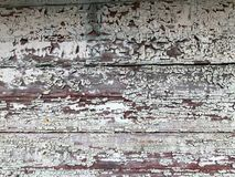 Texture of a black gray old dilapidated wooden wall, a fence with pieces of old shabby exfoliated paint from horizontal worn-out r. Otten boards with cracks and Royalty Free Stock Photos