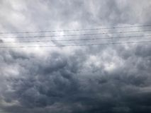 Texture black tensioned high-voltage wires for electricity against a background of dark blue sullen storm stormy sky rain clouds stock photo