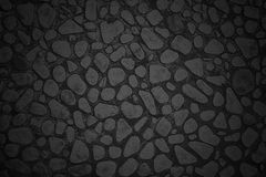 Texture of a black wall of small stones with rounded edges Stock Photo