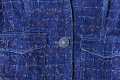 Texture of blue denim with gold threads. Beautiful blue button, pockets Stock Image