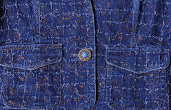 Texture of blue denim with gold threads. Beautiful blue button, pockets Stock Photos
