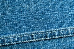 Texture of blue denim material with a seam close-up stock photo