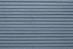 Texture of blue and gray corrugated metallic surface. Blue ribbed background with stripes, straight lines. Modern pattern of blue. Metal jalousie royalty free stock images