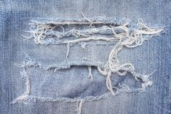 Texture blue jeans with ripped on background, hole and white threads destroyed patterns on denim stock photography