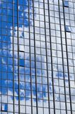 Texture of blue shiny glass skyscraper windows, buildings with reflection of white clouds and sky. The background royalty free stock photography