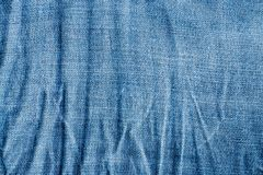 Texture of blue wrinkled faded jeans textile closeup.  Stock Photo