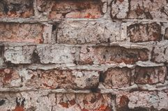 Texture of aged red brick wall painted white color with cracked weathered structure close-up. Texture of brick wall with cracked weathered structure red white stock photography
